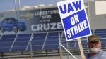 A picketer carries sign at one of the gates outside the closed General Motors automobile assembly plant in Lordstown, Ohio, on Sept. 16, 2019. (Keith Srakocic / AP)