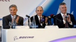 Qatar Airways CEO Akbar Al Baker, center, applauds with Boeing CEO Kevin McAllister, right, and Boeing vice chairman Ray Conner during a news conference before a delivery ceremony for a new Boeing 747-8 freighter to Qatar Airways, Monday, Sept. 25, 2017, at Boeing's delivery center in Everett, Wash. (AP Photo/Elaine Thompson)