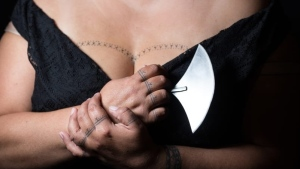 Cora DeVos holds a traditional Inuit knife and shows off the traditional Inuit tattoos she has on her chest, wrists and fingers. (CNN via Little Inuk Photography)