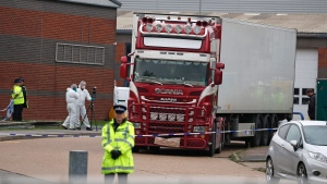 Police forensic officers attend the scene after a truck was found to contain a large number of dead bodies, in Thurrock, South England, Wednesday Oct. 23, 2019. (AP Photo/Alastair Grant)