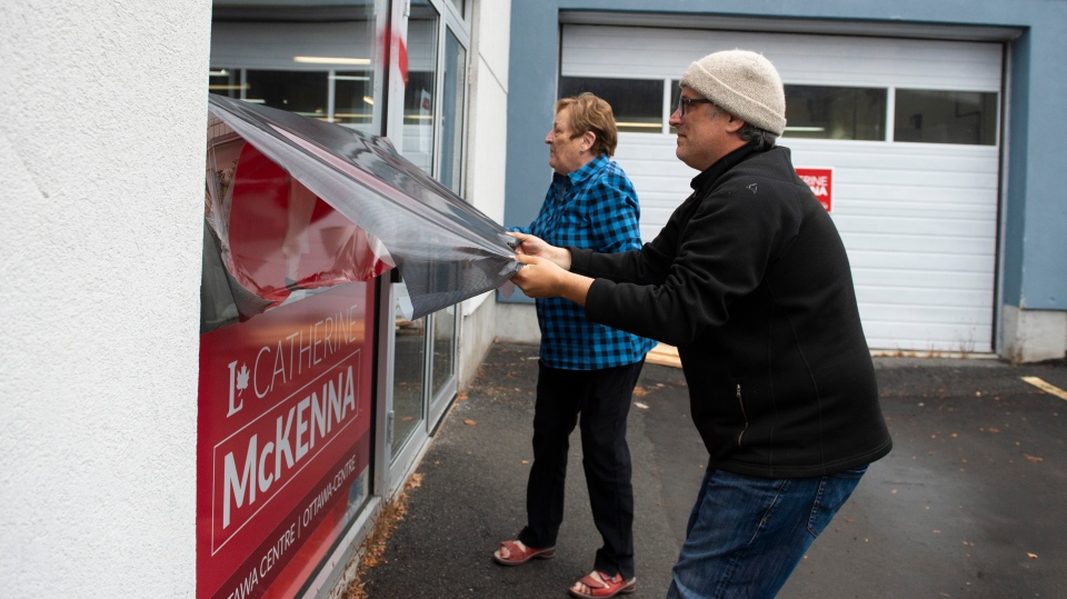 Campaign team members remove a window decal that was defaced with a misogynistic slur on the campaign office of re-elected Liberal MP Catherine McKenna, in Ottawa, on Thursday, Oct. 24, 2019. (THE CANADIAN PRESS/Justin Tang)