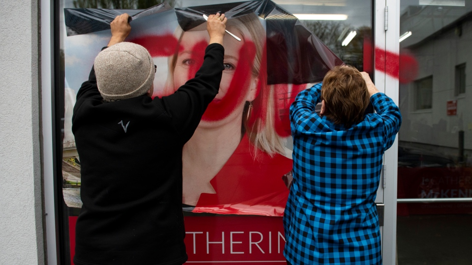 Campaign team members remove a window decal that was defaced with a misogynistic slur on the campaign office of re-elected Liberal MP Catherine McKenna, in Ottawa, on Thursday, Oct. 24, 2019. THE CANADIAN PRESS/Justin Tang