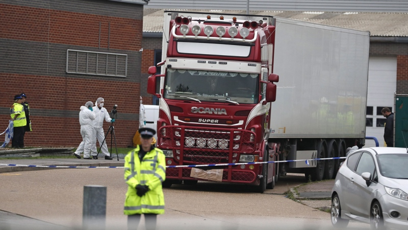 In this Oct. 23, 2019, file photo, police forensic officers attend the scene after a truck was found to contain a large number of dead bodies, in Thurrock, England. (Alastair Grant / AP)