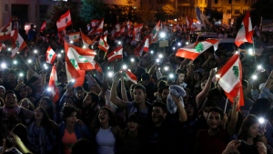 Anti-government protesters use the light on their phones and shout slogans against the Lebanese government during a protest in Beirut, Lebanon, Saturday, Oct. 26, 2019. (AP Photo/Bilal Hussein)