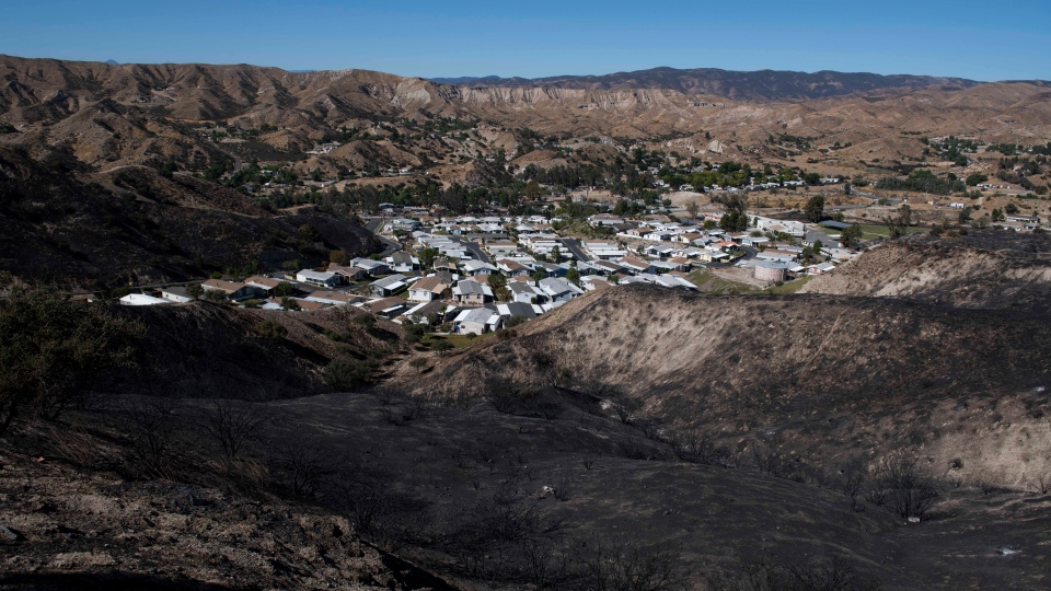 A mobile home community sits between charred hillsides from the Tick Fire, Thursday, Oct. 25, 2019, in Santa Clarita, Calif. (AP Photo/ Christian Monterrosa)