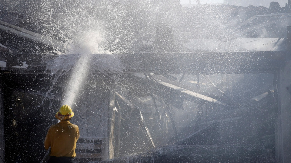 A firefighter tries to put out a residence fire caused by a wildfire Friday, Oct. 25, 2019, in Santa Clarita, Calif. (AP Photo/Marcio Jose Sanchez)
