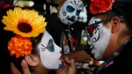 Ximena Bobadilla Ortiz, left, gets her face painted by Belen Marquez before the Catrinas parade down Mexico City's iconic Reforma avenue during Day of the Dead celebrations, Saturday, Oct. 26, 2019. (AP Photo/Ginnette Riquelme)