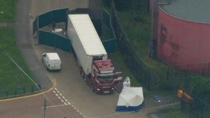 In this Oct. 23, 2019, file photo, police forensic officers attend the scene after a truck was found to contain a large number of dead bodies in Thurrock, South England. (UK Pool via AP, File)
