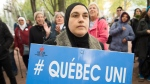 People hold up signs during a demonstration against Bill 21 in Montreal, Sunday, October 6, 2019. The controversial Quebec secularism law bans some public-sector employees from wearing religious symbols in the workplace. THE CANADIAN PRESS/Graham Hughes