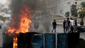 Anti-government protesters set fire to tires to block a highway that links the capital Beirut to northern Lebanon during a protest against the Lebanese government in Zouk Mosbeh, north of Beirut, Lebanon, Monday, Oct. 28, 2019. (AP Photo/Hassan Ammar)