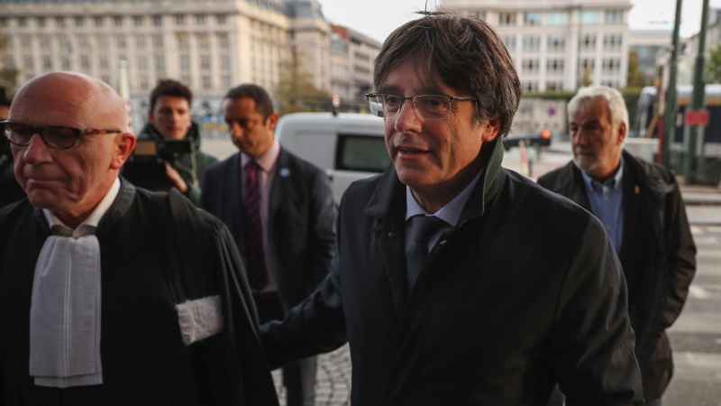 Catalonia's former regional president Carles Puigdemont, right, arrives with his lawyer Paul Bekaert to the Justice Palace in Brussels, Tuesday, Oct. 29, 2019. (AP Photo/Francisco Seco)