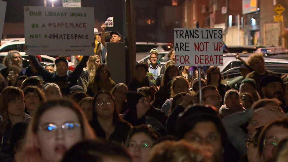 Protesters waved signs and used a microphone to read works by trans writers.