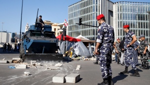 Police remove stones set up by anti-government protesters to block a main road in Beirut, Lebanon, Wednesday, Oct. 30, 2019. (AP Photo/Bilal Hussein)