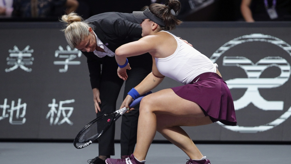 Bianca Andreescu tries to stand after an injury
