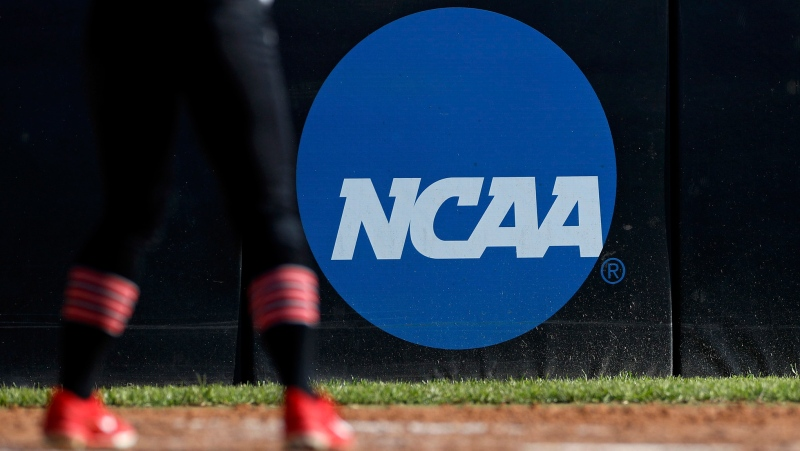 FILE - In this April 19, 2019, file photo, an athlete stands near a NCAA logo during a softball game in Beaumont, Texas. (AP Photo/Aaron M. Sprecher, File)