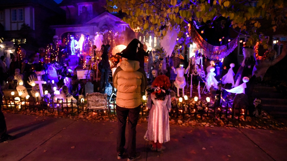 People go trick-or-treating at a decorated home in the Glebe neighbourhood in Ottawa on Halloween, Monday, Oct. 31, 2016 in Ottawa. (Justin Tang/THE CANADIAN PRESS)