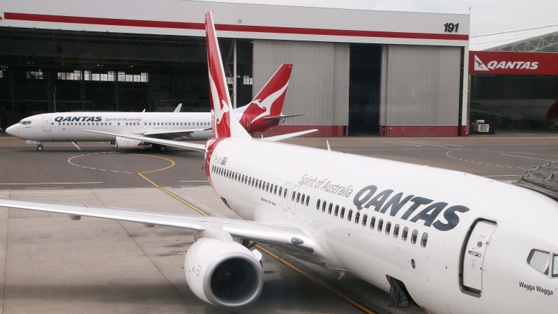 FILE - In this Feb. 26, 2015, file photo, a Qantas 737 plane maneuvers behind another 737 parked at a gate at Sydney Airport in Sydney. (AP Photo/Rick Rycroft, File)
