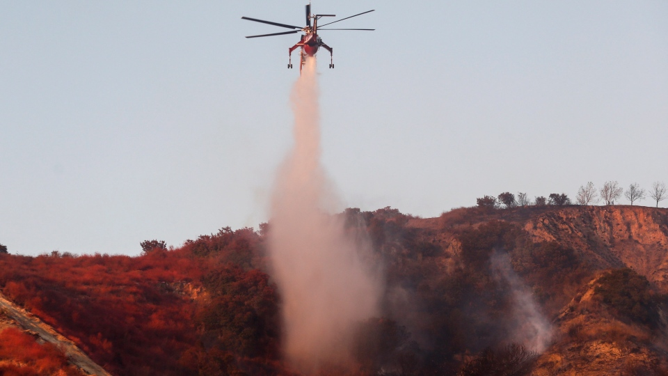 A helicopter drops water to put out hotspots in Simi Valley, Calif., Wednesday, Oct. 30, 2019. (AP Photo/Ringo H.W. Chiu)