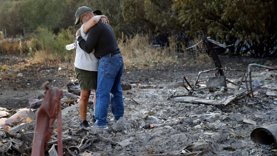 Justo and Bernadette Laos hug while looking through the charred remains of the home they rented that was destroyed by the Kincade Fire near Geyserville, Calif., Thursday, Oct. 31, 2019. (AP Photo/Charlie Riedel)