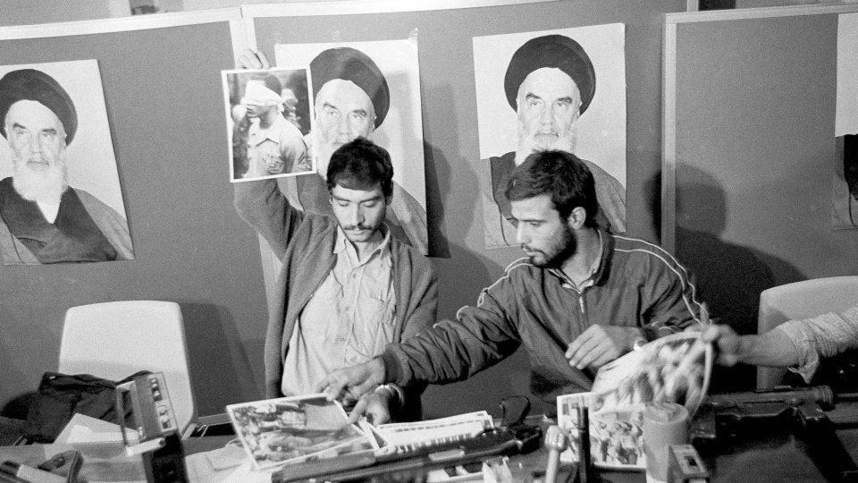 In this Nov. 5, 1979, file photo, Ebrahim Asgharzadeh, left, a representative of the Iranian students who stormed the U.S. Embassy on Nov. 4, holds up a portrait of one of the blindfolded hostages, during a news conference in the embassy in Tehran. Posters of the Islamic Revolution leader Ayatollah Ruhollah Khomeini adorn the wall. The man at right is unidentified. Speaking to The Associated Press ahead of the 40th anniversary of the attack, Asgharzadeh acknowledged that the repercussions of the crisis still reverberate as tensions remain high between the U.S. and Iran over Tehran's collapsing nuclear deal with world powers. (AP Photo/File)