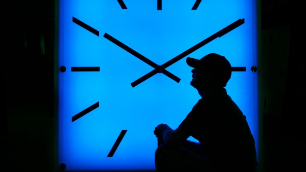 FILE - In this Oct. 30, 2008, file photo, Electric Time Company employee Dan Lamoore adjusts the color on a 67-inch square LED color-changing clock at the plant in Medfield, Mass.  (AP / Elise Amendola)