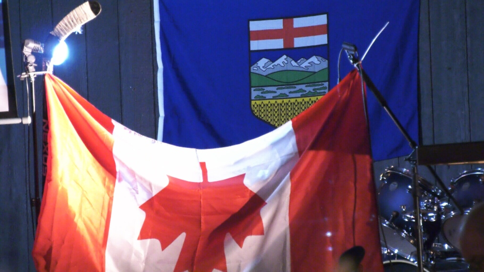 A Canadian flag is displayed upside down at a Wexit rally. (CTV)