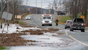 St-Joseph-de-Beauce workers block the flooded road, Friday, November 1, 2019 in St-Joseph-de-Beauce, Que. Heavy rains and strong winds flooded the Chaudiere river. THE CANADIAN PRESS/Jacques Boissinot