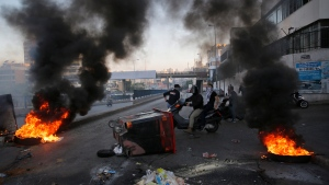 Anti-government protesters ride their scooters as they block a main highway that links to the airport by burned tires and garbage containers, during ongoing protests against the Lebanese government, in Beirut, Lebanon, Monday, Nov. 4, 2019. (AP Photo/Hussein Malla)