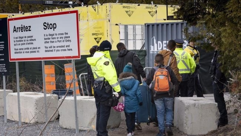 A family, claiming to be from Columbia, is arrested by RCMP officers as they cross the border into Canada from the United States as asylum seekers, on April 18, 2018. near Champlain, N.Y. THE CANADIAN PRESS/Paul Chiasson