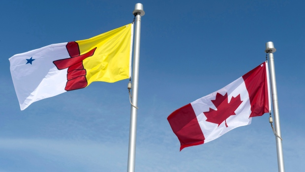 The Nunavut flag and the Canadian flag are seen Saturday, April 25, 2015 in Iqaluit, Nunavut. (THE CANADIAN PRESS / Paul Chiasson)