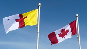 The Nunavut flag and the Canadian flag are seen Saturday, April 25, 2015 in Iqaluit, Nunavut. THE CANADIAN PRESS/Paul Chiasson