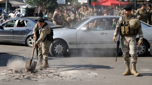 A soldier removes remains of burnt tires placed by anti-government protesters to block a road, as others stand guard in Hazmiyeh, a suburb of Beirut, Lebanon, Tuesday, Nov. 5, 2019. (AP Photo/Bilal Hussein)