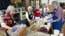 Volunteers making Christmas pudding
