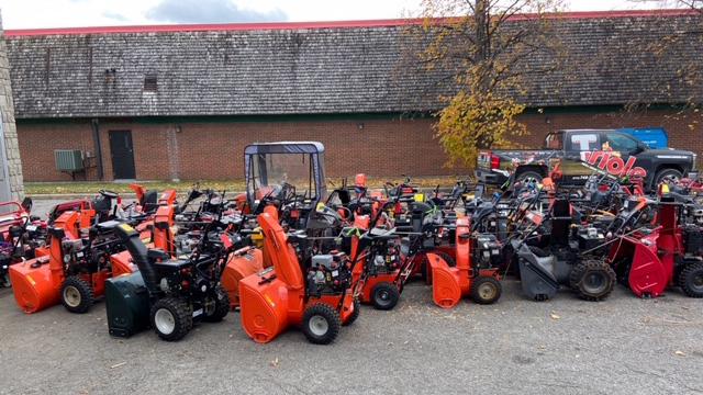 Long line of snow blowers waiting for maintenance
