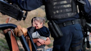 Framed by heavily armed Mexican authorities, relatives of the LeBaron family mourn at the site where nine U.S. citizens, three women and six children related to the extended LeBaron family, were ambushed near Bavispe, at the Sonora-Chihuahua border, Mexico, Wednesday, Nov 6, 2019. (AP Photo/Marco Ugarte)