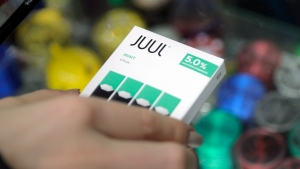 In this Dec. 20, 2018, file photo a woman buys refills for her Juul at a smoke shop in New York. (AP Photo/Seth Wenig, File)
