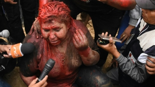 The mayor of the Bolivian town of Vinto, Patricia Arce, speaks to the press as she is being humiliated by a mob of opposition supporters who forcibly cut her hair and covered her in paint. (AFP)