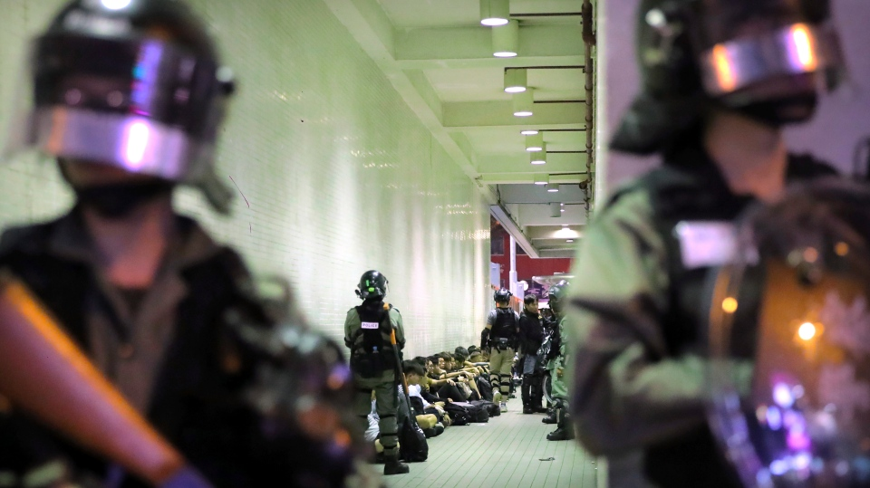 In this Saturday, Nov. 2, 2019, file photo, police in riot gear stand over people detained during a protest in Hong Kong. (AP Photo/Kin Cheung, File)