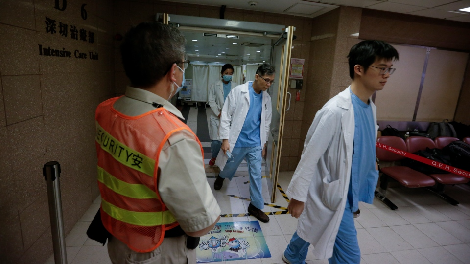 Hospital staff walk out from the ICU ward where a university student who critically injured during a protest, is treated at Queen Elizabeth Hospital in Hong Kong, Friday, Nov. 8, 2019. (AP Photo/Dita Alangkara)