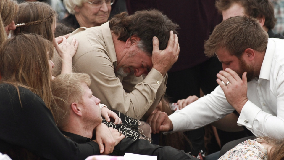 The father of Dawna Ray Langford who was killed in an ambush earlier this week along with two of her son, is comforted by family and friends during a funeral service in La Mora, Mexico, Thursday, Nov. 7, 2019. (AP Photo/Christian Chavez)