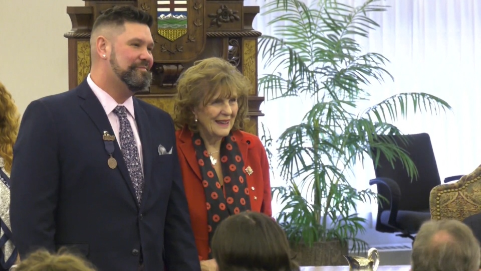 Dale Parkin stands with Lieutenant Governor Lois Mitchel after receiving an award for his bravery from the Royal Canadian Human Association.