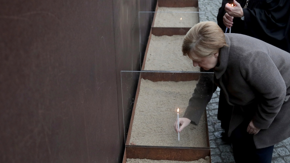 German Chancellor Angela Merkel places a candle at the Berlin Wall Memorial after a memorial service for the 30th anniversary of the fall of the Wall in Berlin, Germany, Saturday, Nov. 9, 2019. (AP Photo/Michael Sohn)