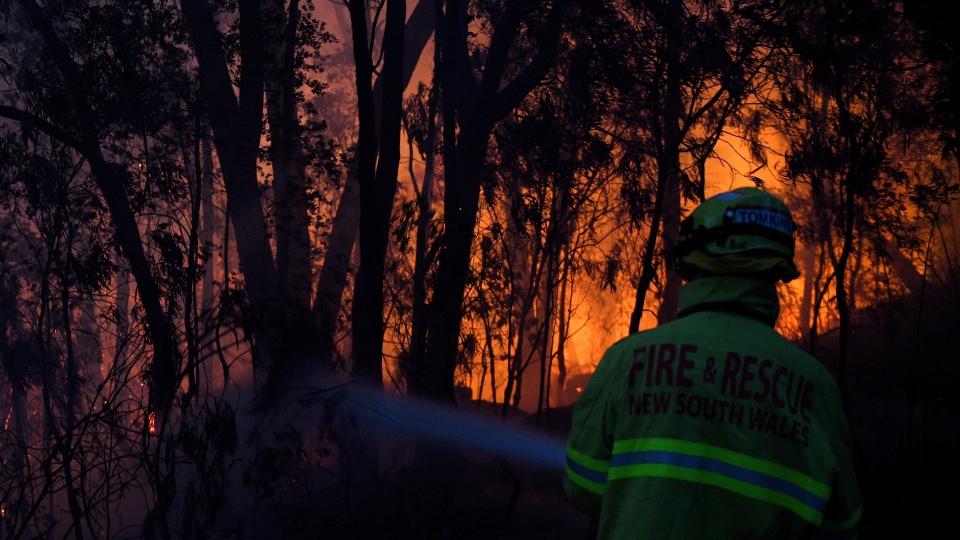 Fire and Rescue NSW firefighters conduct property protection as a bushfire burns close to homes on Railway Parade in Woodford NSW, Friday, Nov. 8, 2019. (Dan Himbrechts/AAP Image via AP)