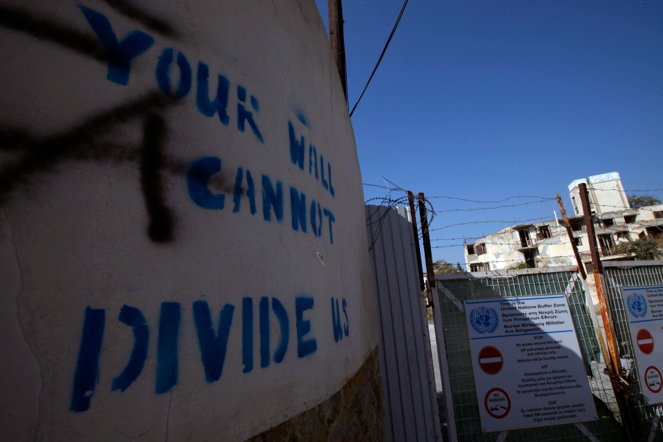 "n this photo taken on Wednesday Nov. 6, 2019, graffiti on a wall reading ""Your wall can not divide us"" is seen at the U.N buffer zone by a fence that divides the Greek Cypriot south and the Turkish Cypriot north, in divided capital Nicosia, Cyprus. (AP Photo/Petros Karadjias)"