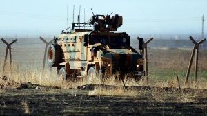 In this photo taken from the outskirts of the village of Alakamis, in Idil province, southeastern Turkey, a Turkish army vehicles is driven in Turkey after conducting a joint patrol with Russian forces in Syria, Friday, Nov. 8, 2019. (AP Photo/Mehmet Guzel)