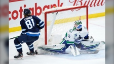 Winnipeg Jets' Kyle Connor (81) goes high to score on Vancouver Canucks goaltender Thatcher Demko (35) during third period NHL action in Winnipeg, Friday, Nov. 8, 2019. (Source: The Canadian Press/John Woods)