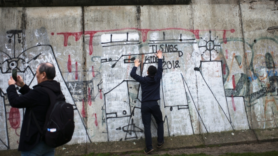 Tourist take photos at remains of the Berlin Wall after commemorations celebrating the 30th anniversary of the fall of the Berlin Wall at the Wall memorial site at Bernauer Strasse in Berlin, Saturday, Nov. 9, 2019. (AP Photo/Markus Schreiber)