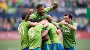 Seattle Sounders defender Roman Torres, top, and teammates mob defender Kelvin Leerdam, centre, (obscured) after scoring against the Toronto FC during second half MLS Cup soccer action in Seattle on Sunday, Nov. 10, 2019. THE CANADIAN PRESS/Jonathan Hayward