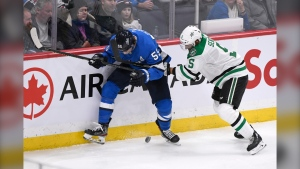 Winnipeg Jets' Mark Scheifele (55) and Dallas Stars' Andrej Sekera (5) battle for the puck during third period NHL action in Winnipeg on Sunday, Nov. 10, 2019. (Source: The Canadian Press/Fred Greenslade)