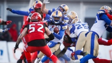 Winnipeg Blue Bombers' Janarion Grant, centre, runs the ball as Calgary Stampeders' Riley Jones closes in during CFL West Semifinal football action in Calgary, Sunday, Nov. 10, 2019. (THE CANADIAN PRESS/Jeff McIntosh)